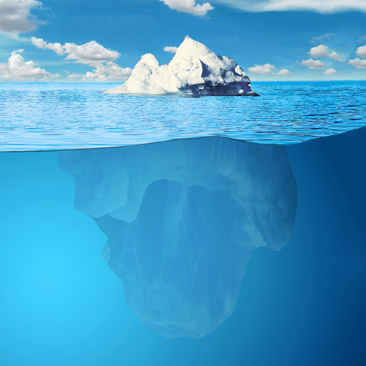 A small tip of an iceberg above the water surface and a big part of the iceberg below to illustrate subconscious mind and hypnosis for social anxiety