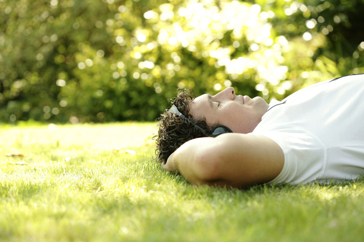 Relaxed man lying in the grass, illustrating the article titled How I overcame social anxiety in just one hour.