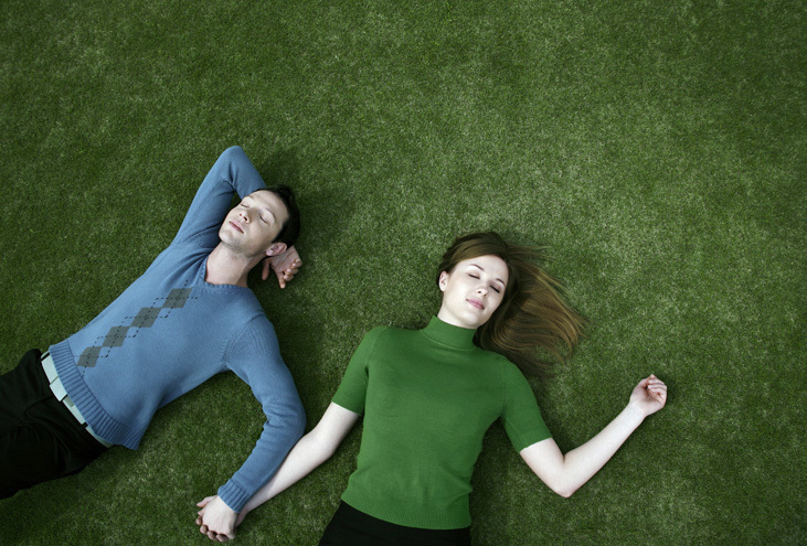 couple relaxing in the grass to illustrate how to overcome social anxiety with relaxation