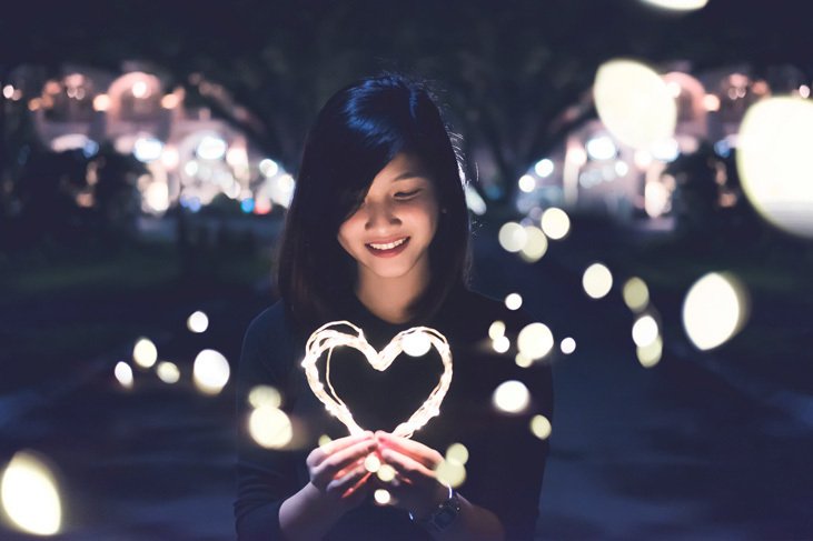 girl holding a light in the shape of heart to illustrate how to cope with social anxiety through love for people